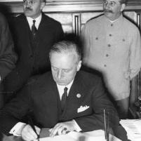 28 septiembre 1939. Firma del Tratado de Amistad, Cooperación y Frontera germano-soviético. El Ministro de Relaciones Exteriores del Reich v. Ribbentrop durante la firma. Detrás, Josif Stalin y el Comisionado de Asuntos Exteriores Viacheslav Mólotov.