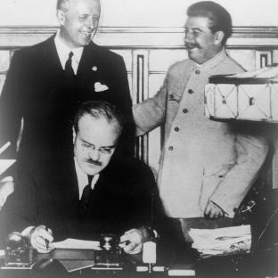 28 septiembre 1939. Firma del Tratado de Amistad, Cooperación y Frontera germano-soviético. El ministro de Relaciones Exteriores soviético, Viacheslav Mólotov firmando. Detrás de él, el Ministro de Relaciones Exteriores del Reich Joachim von Ribbentrop y Josif Stalin.